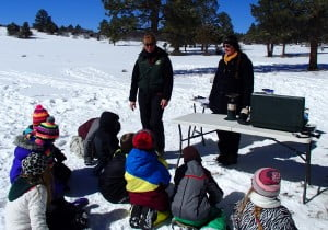 Anne from USFS and Rhianna with the UWP discuss with students how scientist monitor the snowpack to predict water needs for the following year.
